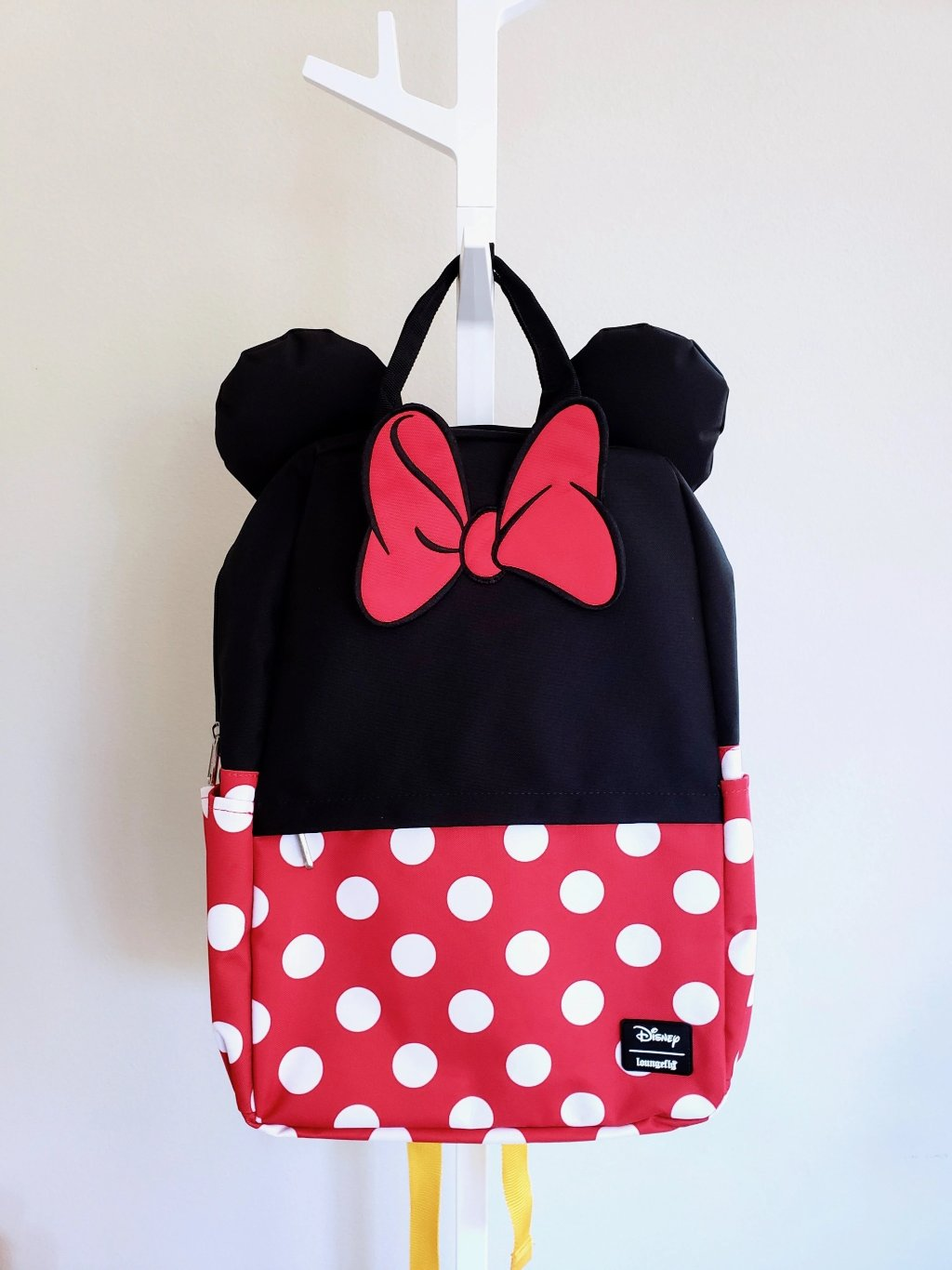 Loungefly Disney Minnie Mouse black, red and white polka dotted backpack with Minnie ears and red bow. front view