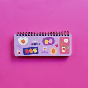 PINKFOOT I Like Carrot Series Weekly Scheduler Spiral Bound Purple Hard Cover with gummy carrots in a food scene front view