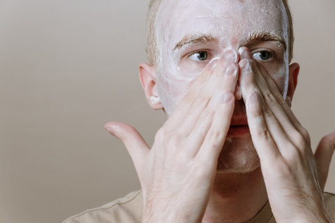 man using scrub to exfoliate skin to look younger