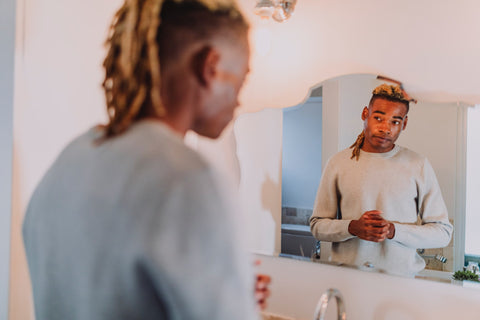 man in the bathroom using skincare products to look younger