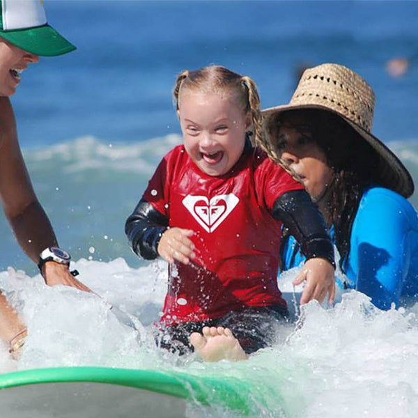 Female Youth with downs syndrome smiling on a green surfboard on a small wave.