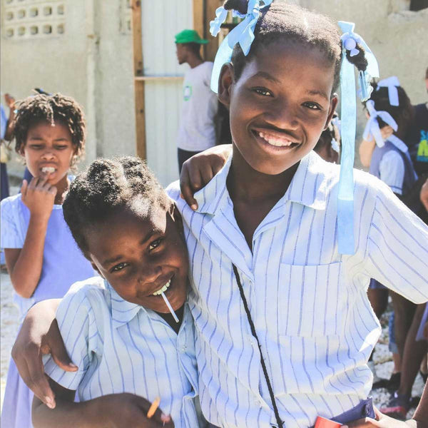 Two haitian female students smiling wearing white school uniforms