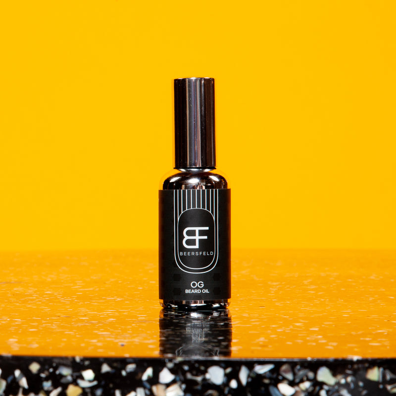 BEERSFELD 50 ml / 1.7 oz Beard Oil. Glass Chrome bottle with dark charcoal label set against Orange