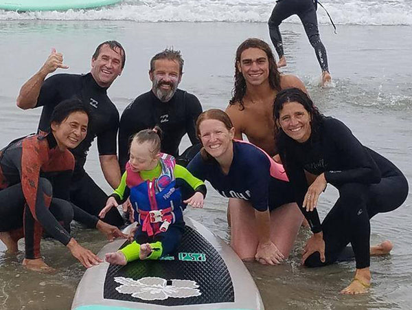 Group of surf instructors on the beach smiling around a youth with downs syndrome on a surfboard.