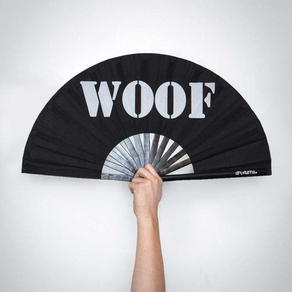 "Black fan with white lettering spelling ""WOOF"" held up by a caucasian arm and hand against grey"