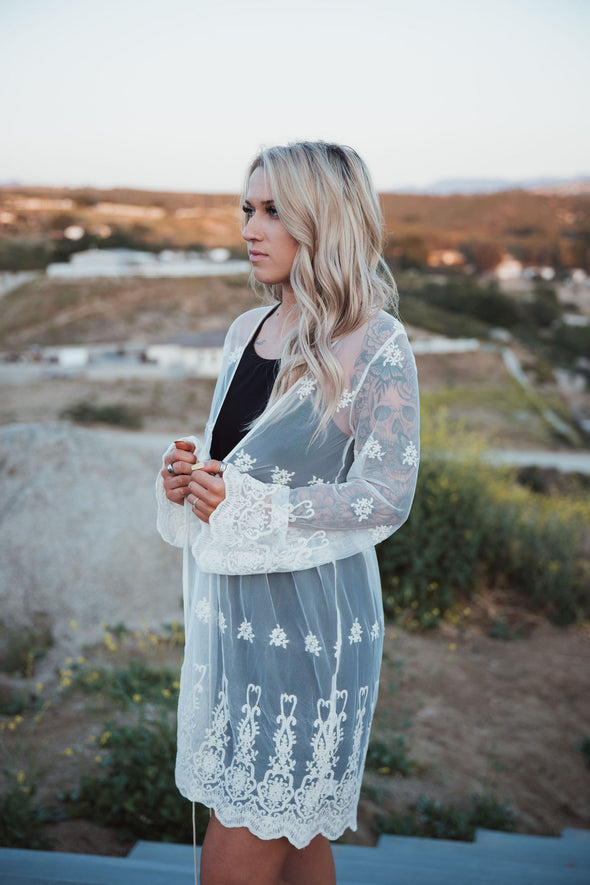 Shop Priscilla Sheer Long Natural Cardigan * Beautiful Lace Design * Tie String Waist with Tassel  * Bell Sleeves * Scalloped Bottom Styled with our Monica Dress. Lexi is 54 wearing a size Medium. 42.00 USD // ShopBellaAllure.com