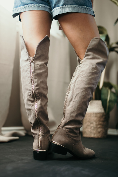 Shop Emory Knee-High Boot This timeless boot has us falling head over boots! This over the knee boot has dainty gold detailing and softest faux suede for a perfect wealthy look. Over the knee  Gold zipper down back  Runs small  Dainty gold detailing 28.00 USD // ShopBellaAllure.com