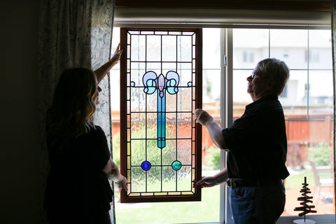 Rebecca Maher and her dad Glenn hanging a stained glass window in the living room