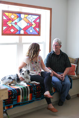 Rebecca Maher, Glenn Maher and cute dog sitting on a bay window, geometric stained glass window behind them