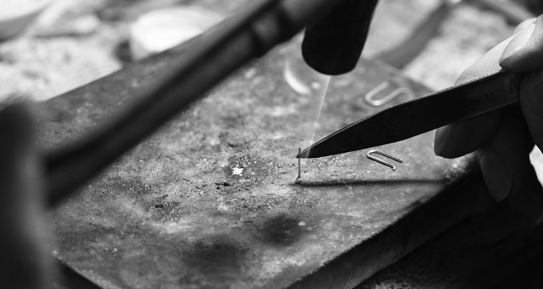 jeweler hands working on littionary's dot earrings