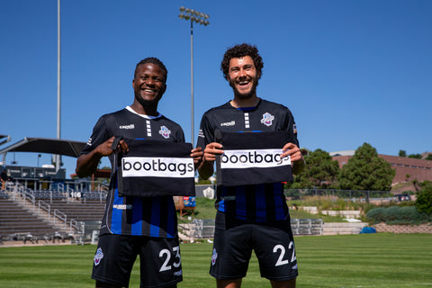 Shane Malcolm (left) and Jordan Schweitzer (right) holding bootbags