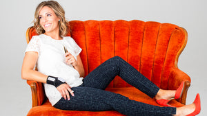 Woman on couch smiling and holding the LashWrap and tweezers for lashing