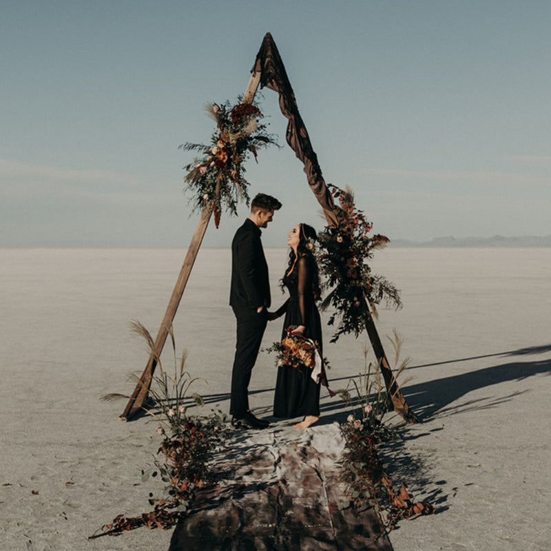 Moody elopement styled-shoot at the Bonneville Salt Flats under a triangle arch