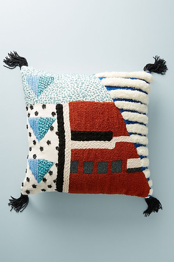 Geometric patterned pillow, blue and red with black tassels