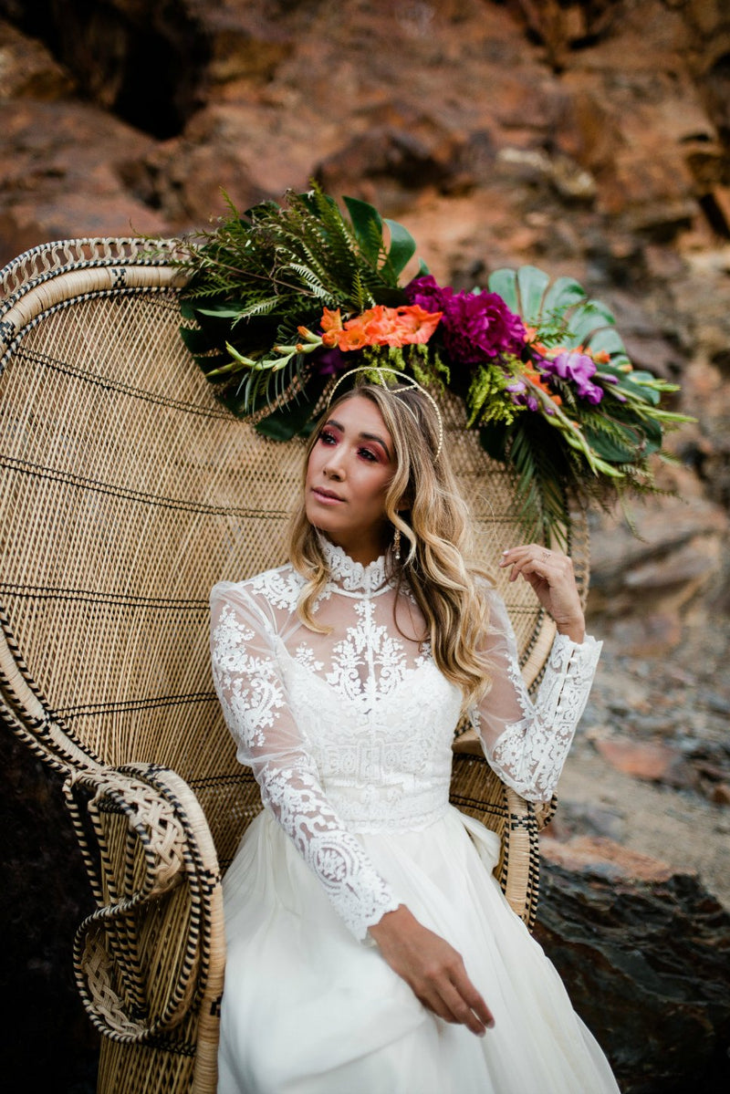 Bride sitting on boho peacock chair with bright florals