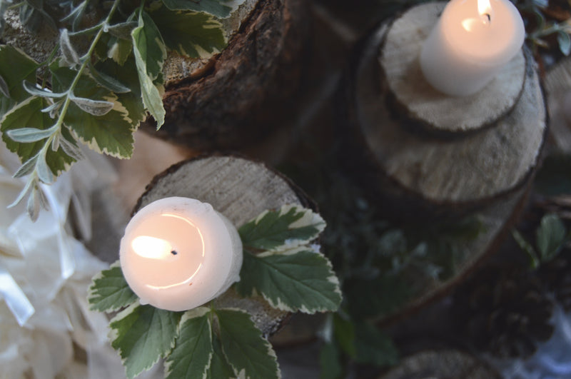 Sliced wood centerpieces with candles and greenery