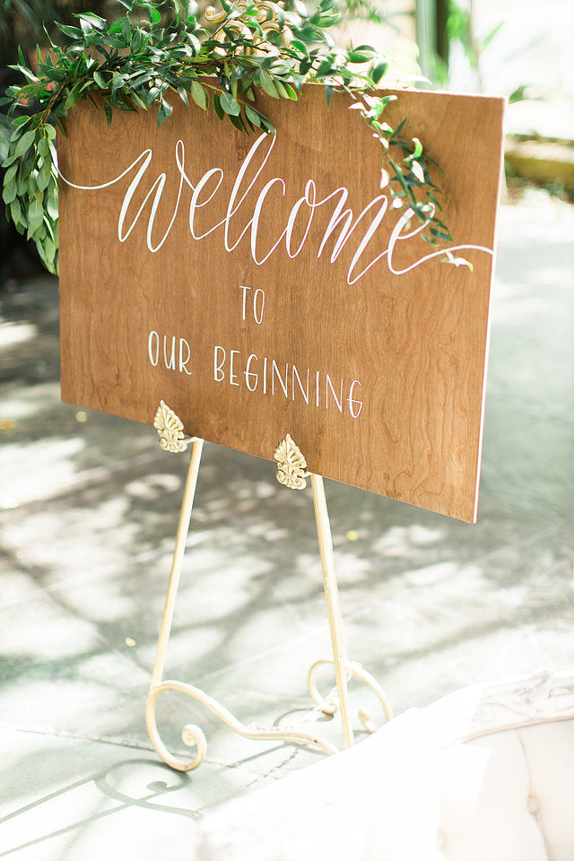 """Welcome to our Beginning"" wooden wedding sign on easel"