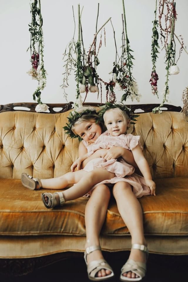 Sisters sitting on vintage mustard love seat