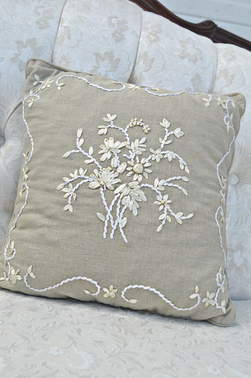 Tan pillow with ivory patterned ribbon embroidery