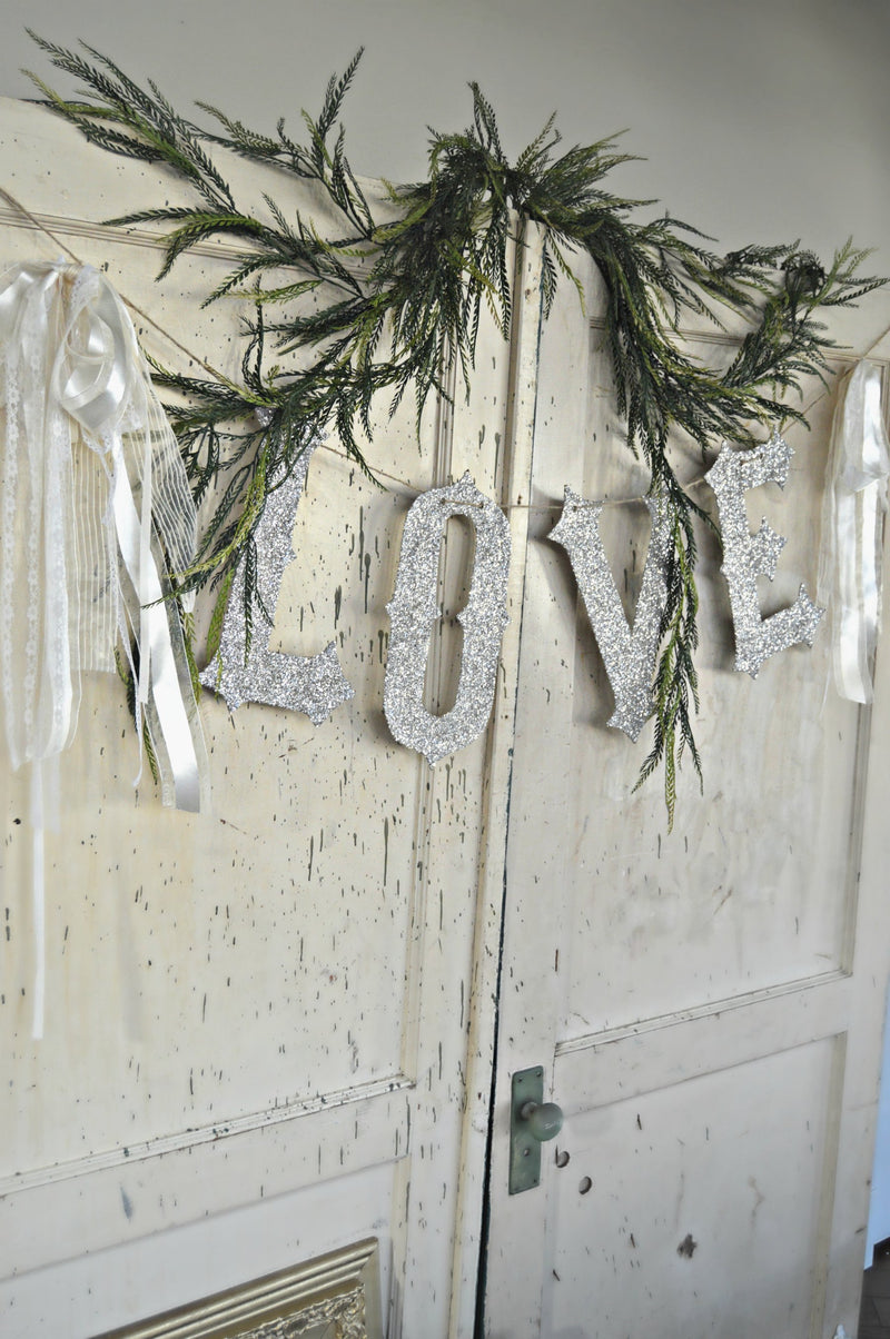 Love banner hung on vintage doors as wedding decor