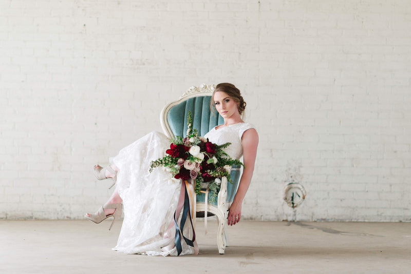 Bride sitting on blue velvet chair