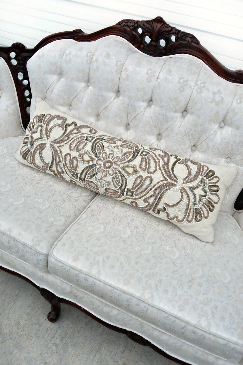 Ivory pillow with light purple, bronze, grey, and white beads