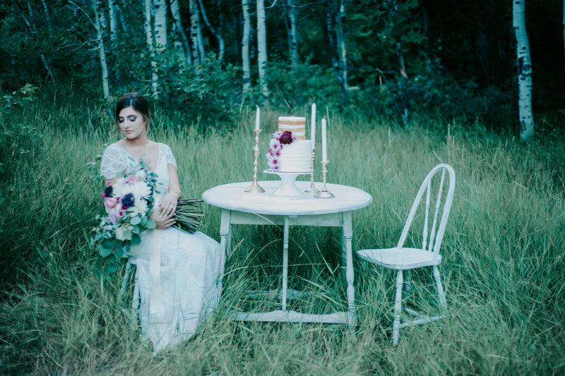 Bride sitting at white cake table in the woods