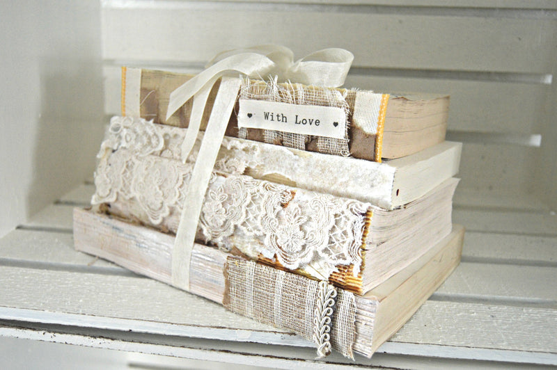 Cream vintage books bundled together for wedding centerpieces