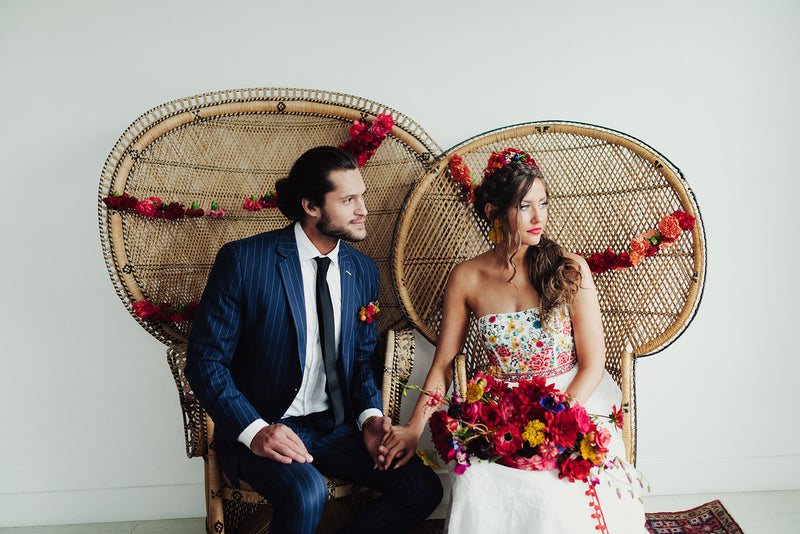 Wedding couple sitting in boho peacock chairs fan back