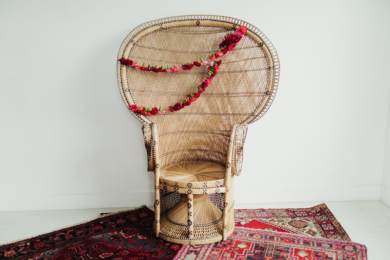 Wicker peacock chair with floral decor and boho rugs
