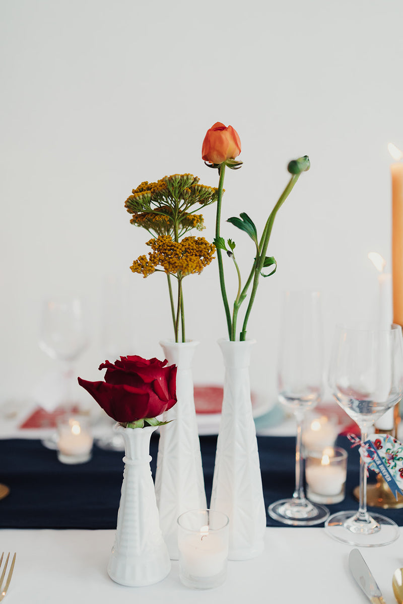 White milk glass vases with florals as centerpieces