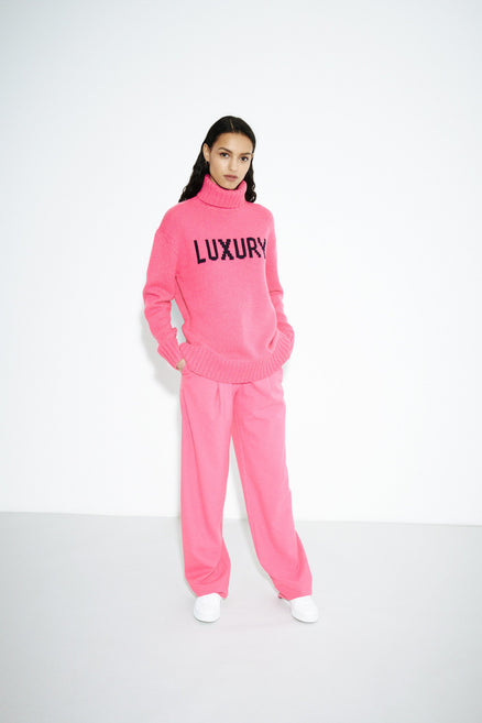 model shot of pink-luxury-cashmere-rollneck-sweater oversized with a ribbed roll neck, hem and cuffs. From Chinti & Parker