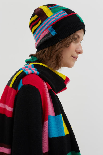 model shot of black-eccentric-wool-cashmere-beanie with abstract brightly coloured intarsia stripes From Chinti & Parker