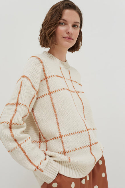 model shot of cream-contrast-check-merino-wool-sweater chunky with alpaca hand-embroidered detail From Chinti & Parker