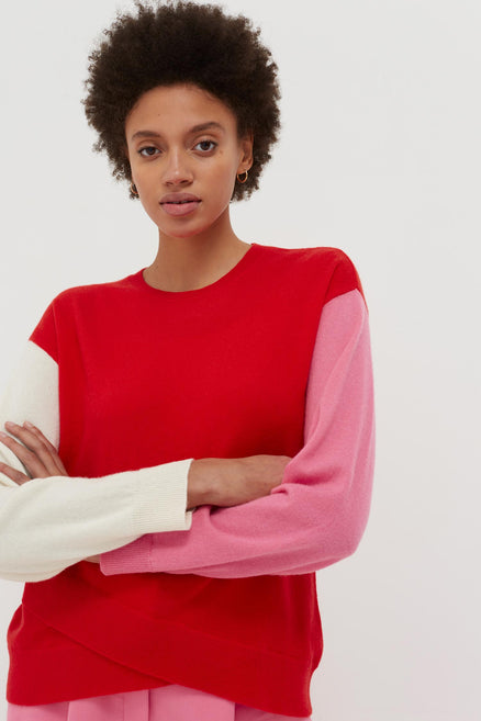 model shot of red-cross-hem-cashmere-sweater crossover hem with colour-block arms, in cream and pink From Chinti & Parker