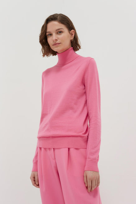 model shot of pink-rollneck-cashmere-pop-sweater Is slim-fitting and lightweight From Chinti & Parker