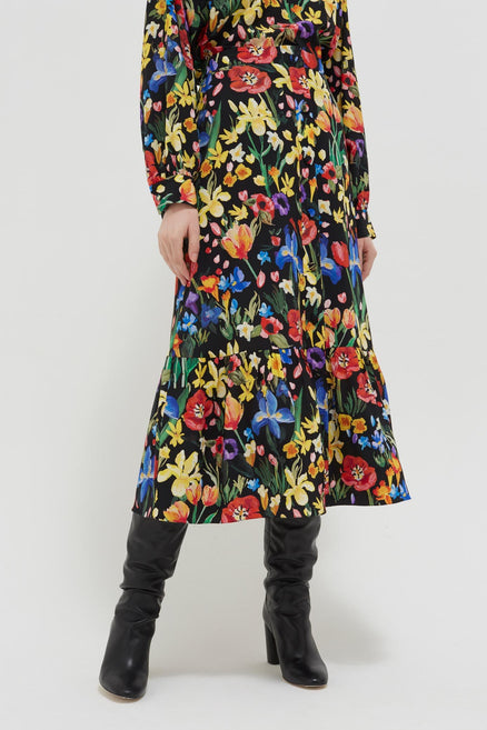 model shot of black-charleston-floral-print-silk-skirt midi length with irises, tulips and daisies From Chinti & Parker
