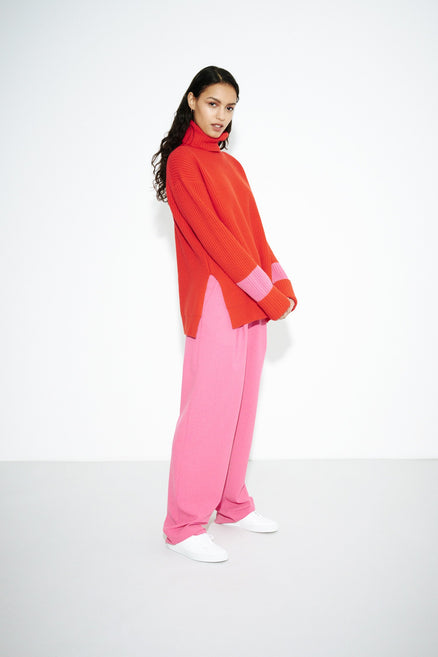 model shot of red-rib-merino-wool-rollneck-sweater in a chunky ribbed-knit; oversized and relaxed From Chinti & Parker