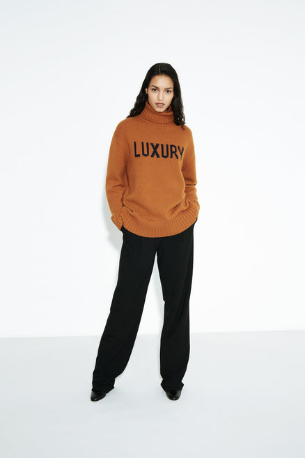 model shot of ginger-luxury-cashmere-rollneck-sweater oversized with a ribbed roll neck, hem and cuffs. From Chinti & Parker