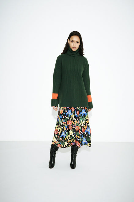 model shot of green-rib-merino-wool-rollneck-sweater in a chunky ribbed-knit; oversized and relaxed From Chinti & Parker