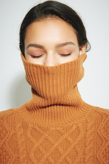 model shot of ginger-pop-aran-merino-wool-sweater chunky with rollneck in a vivid shade of ginger From Chinti & Parker
