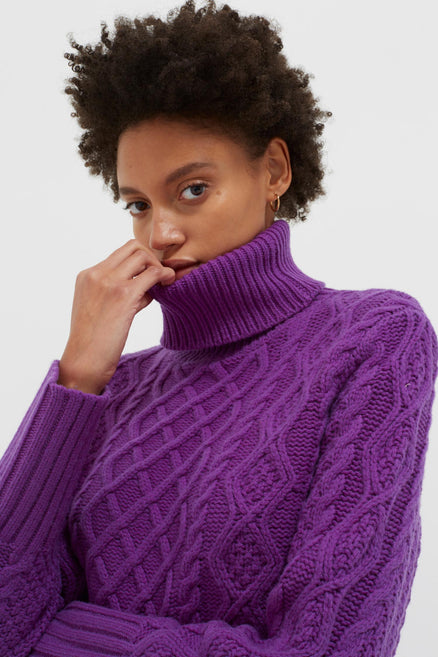 model shot of purple-pop-aran-merino-wool-sweater chunky with rollneck in a vivid shade of purple From Chinti & Parker