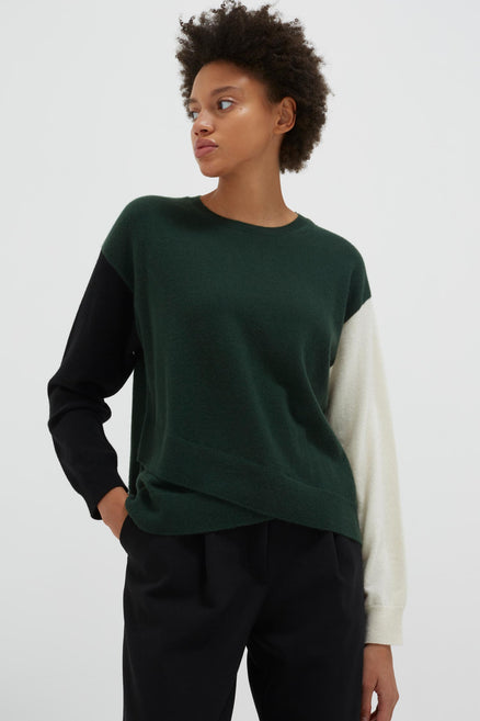 model shot of green-cross-hem-cashmere-sweater crossover hem with colour-block arms, in cream and black From Chinti & Parker