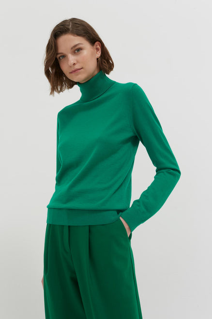 model shot of green-rollneck-cashmere-pop-sweater Is slim-fitting and lightweight From Chinti & Parker