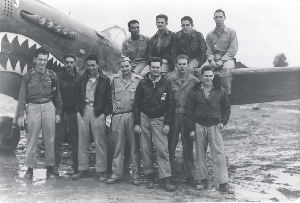 Members of the Flying Tigers standing around one of their P-40 shark-faced fighter planes.