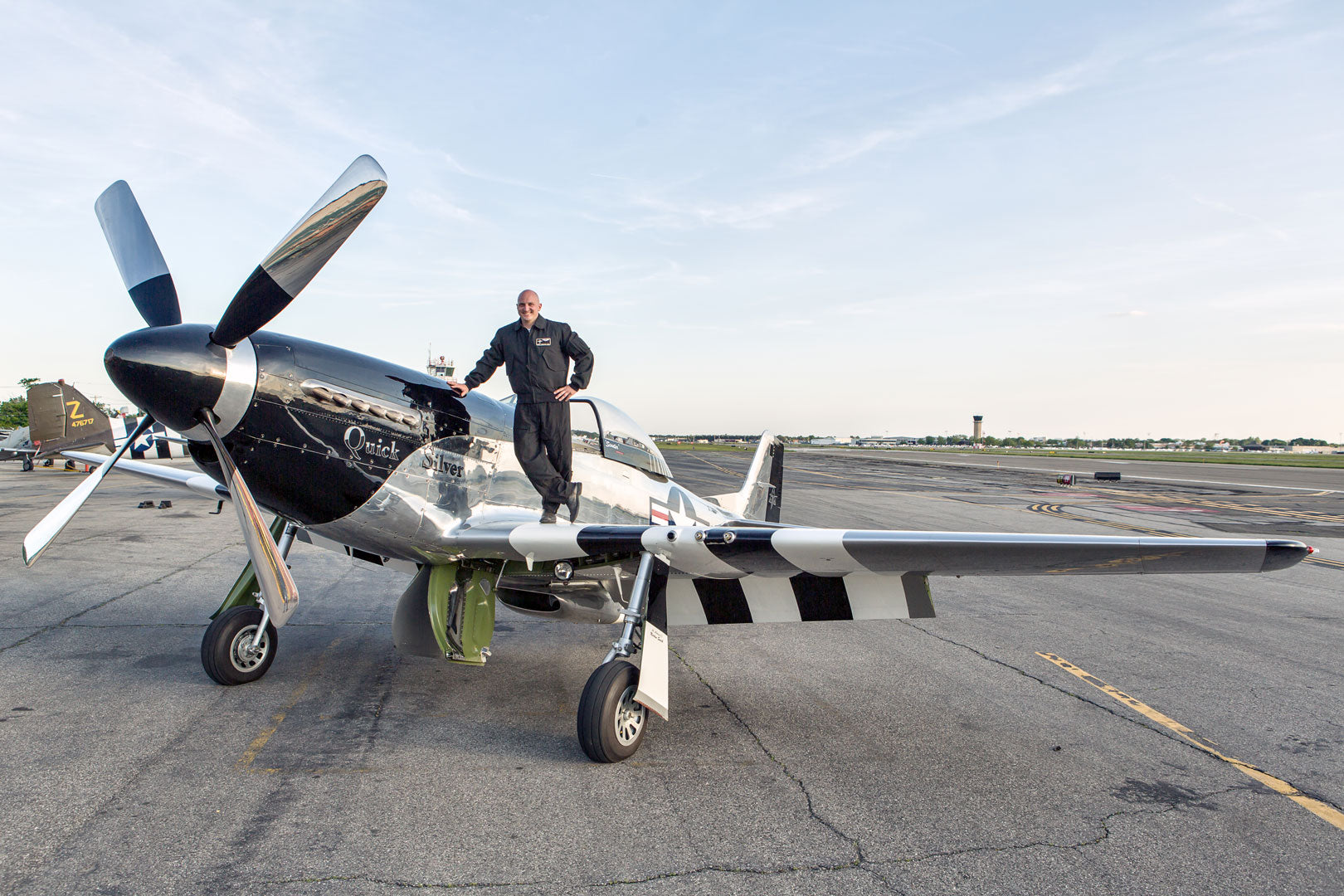 Pilot Scott Yoak standing on the wing of his P-51 in his Cockpit USA Nomex CWU.