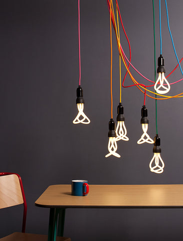 Plumen 001 cluster of light bulbs with coloured cable above a kitchen table