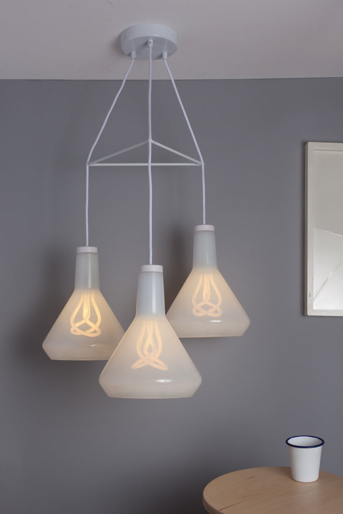 white chandelier with three plumen 002 bulbs in white glass drop top lamp shades