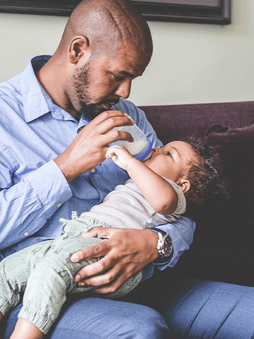 dad feeding his son with a lansinoh bottle