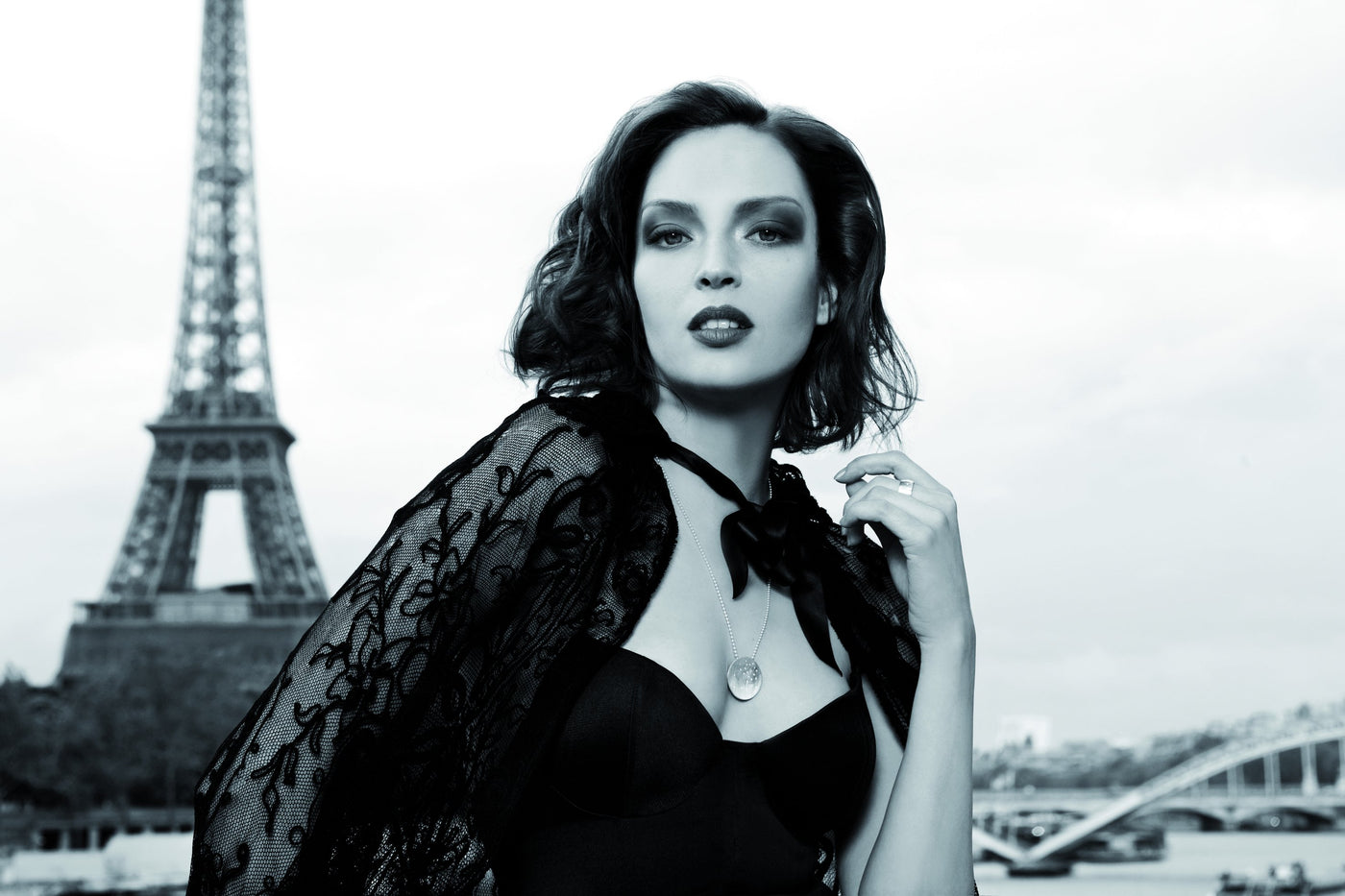 Woman wearing necklace with Eiffel Tower in background